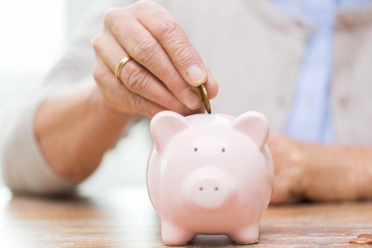 Pensioni, riforma strutturale: donna mette moneta in salvadanaio
